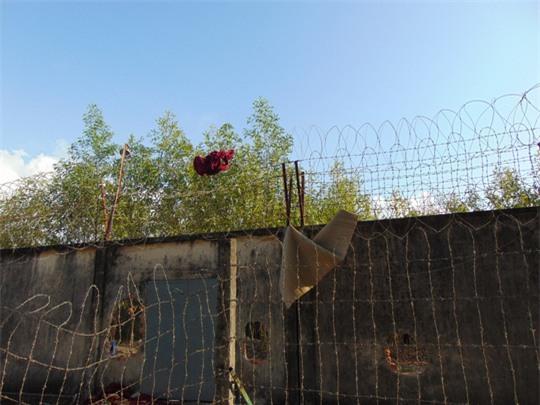 Một số khác dùng chiếu, chăn quấn lại hàng rào dây thép gai để trèo qua