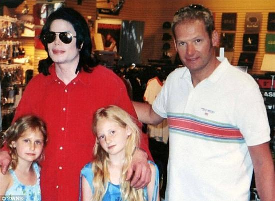 Jackson poses for a photo in 2004 with friend Mark Lester and Lester's two children Harriet and Olivia