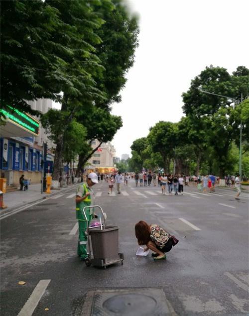 co gai tre cui xuong hot phan cho tren duong cho vao thung rac - 1
