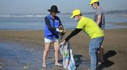 Thu Minh mặc quần đùi, mang dép lào dọn rác ở bãi biển
