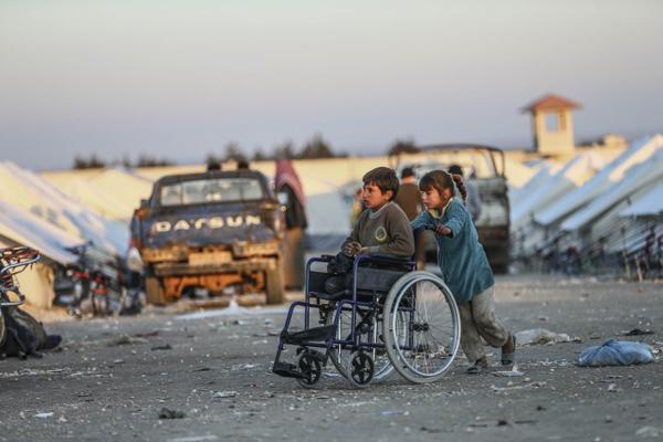 Một em bé di cư khác đang đẩy chiếc xe chở cậu bé bị cụt chân. Hai đứa trẻ đều sống tại lều tạm của người di cư ở biên giới Syria, gần thị trấn Aleppo
