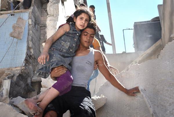 Một bé gái được đưa ra khỏi đống đổ nát trong cuộc không kích của quân đội Syria ở Aleppo tháng 7/2016