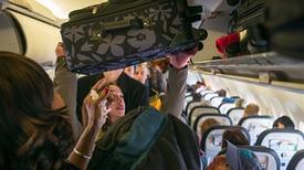 Có nên giúp người khác để hành lý vào khoang trên máy bay?