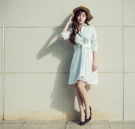 Midu diện chiếc váy trắng thắt eo kiểu cách phía trước kết hợp giày cao gót và mũ cói. Tất cả đều tạo nên cho cô vẻ ngoài trong sáng, nữ tính.