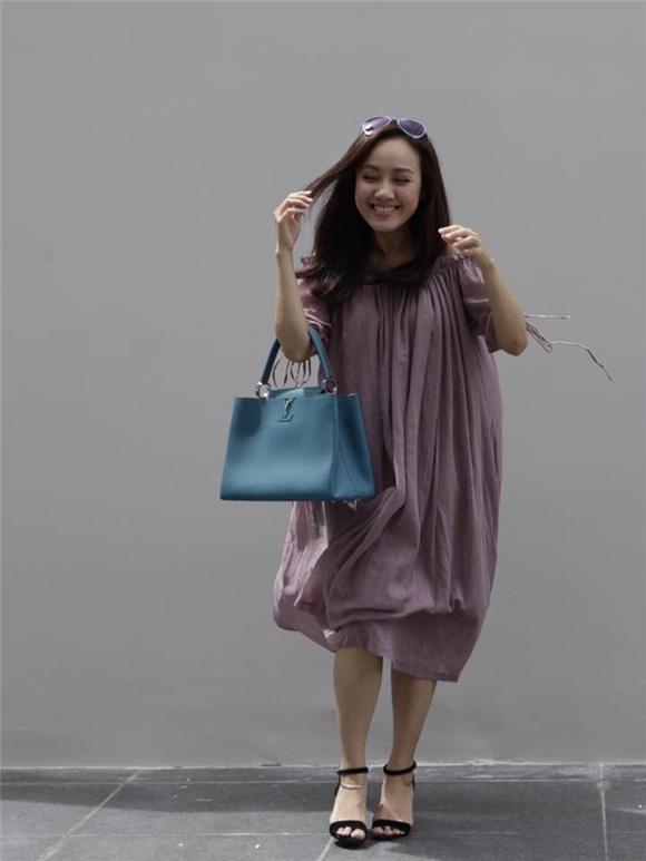 Chiếc túi hàng hiệu Louis Vuitton được cô mix với váy thoải mái ra phố.