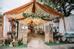 Đôi uyên ương đã chọn phong cách rustic mộc mạc cho ngày trọng đại. Cổng hoa được thiết kế bằng bốn cánh cửa mộc mạc, đính hoa atiso.