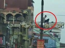 Nam thanh niên ở Hà Nội ngồi vắt vẻo trên cột điện