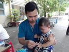 Chồng ẵm con nhỏ ngồi cổng trường đợi vợ thi THPT quốc gia
