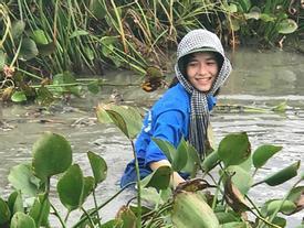Nữ sinh cười rạng rỡ, ngâm mình dọn rác dưới đầm nước