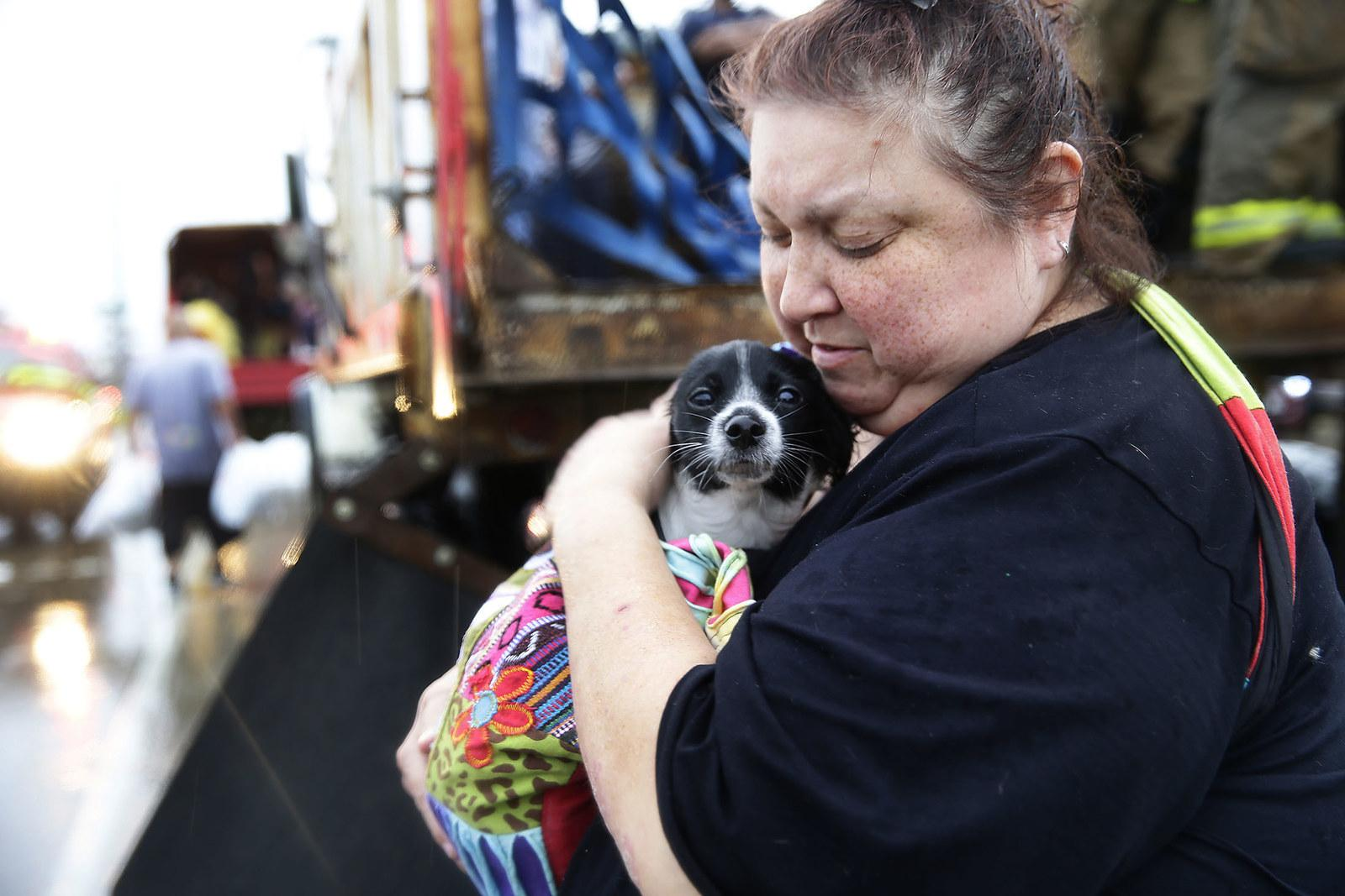 Elma Moreno comforts her dog Simon as they are loaded on to a truck after being evacuated from their flooded apartment in Houston on Aug. 27.