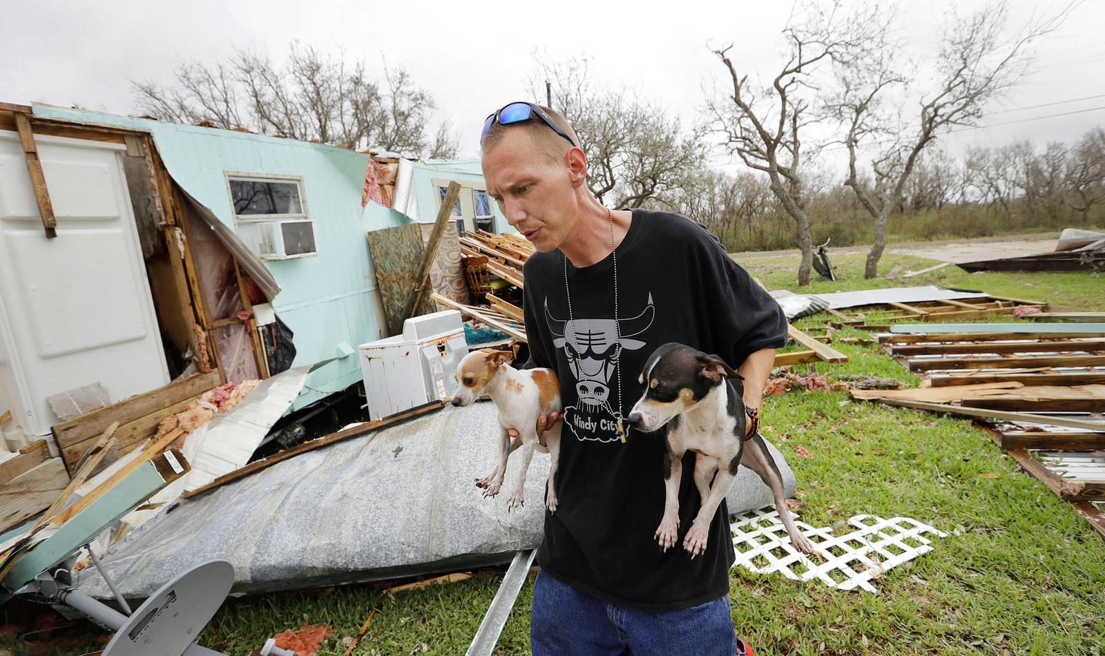 Sam Speights holds two of his dogs as he checks on the damage to his home on Aug. 27, in Rockport, Texas. Speights tried to stay in his home during the storm but had to move to other shelter after his lost his roof and back wall.