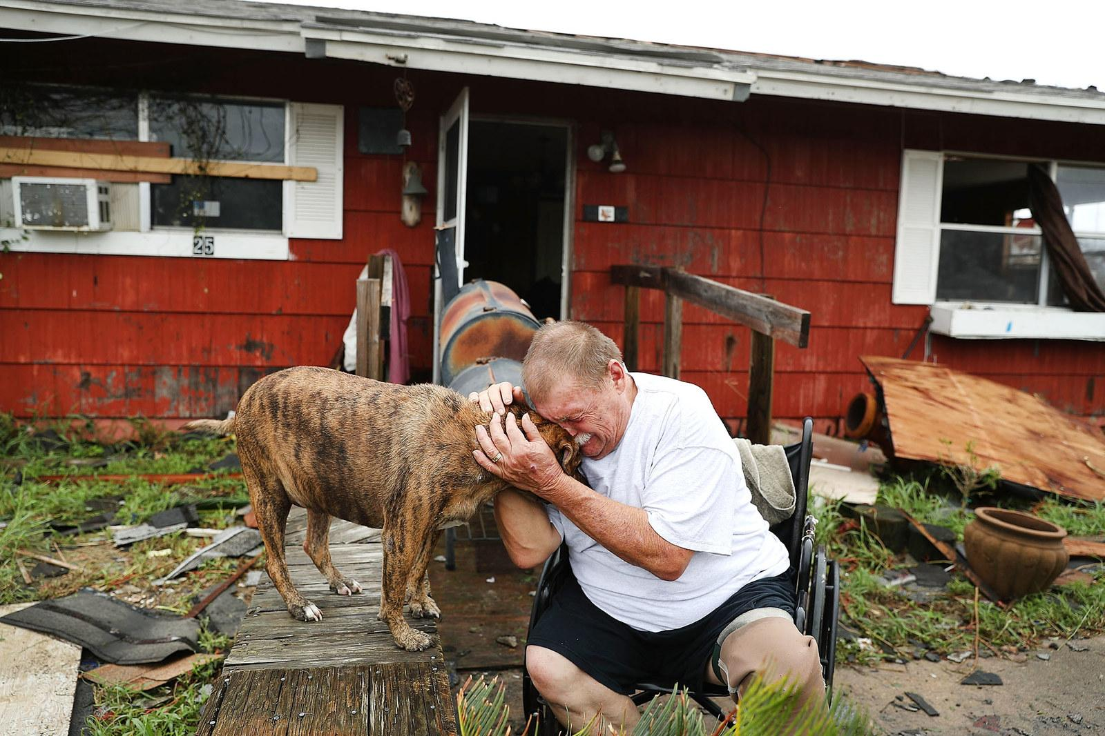 """Steve Culver cries with his dog Otis as he talks about what he said was the """"most terrifying event in his life,"""" when Tropical Storm Harvey blew in and destroyed most of his home while he and his wife took shelter there on Aug. 26, in Rockport, Texas."""