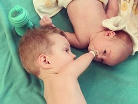 Khoảnh khắc xúc động khi bé trai 3 tuổi không tay chân dỗ dành em trai sơ sinh với núm vú giả