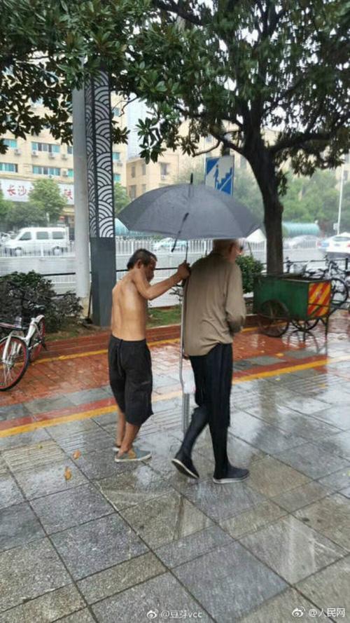Người ăn mày khuyết tật tận tuỵ che ô cho cụ già chống nạng bước đi trong mưa gây xúc động-1