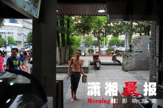 Người ăn mày khuyết tật tận tuỵ che ô cho cụ già chống nạng bước đi trong mưa gây xúc động-4