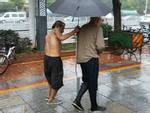 Người ăn mày khuyết tật tận tuỵ che ô cho cụ già chống nạng bước đi trong mưa gây xúc động