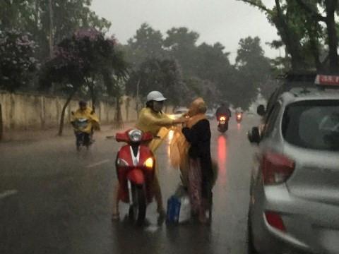 Chàng trai cầm ô che cho bác tài xế thay lốp ôtô giữa cơn mưa lớn-3