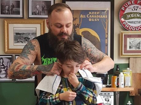 Nằm lăn ra đất để cắt tóc cho cậu bé, hành động này của người thợ đã được cả thế giới tung hô-1
