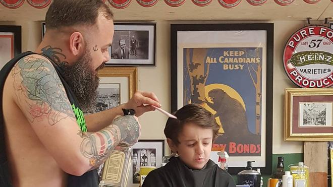 Nằm lăn ra đất để cắt tóc cho cậu bé, hành động này của người thợ đã được cả thế giới tung hô-5