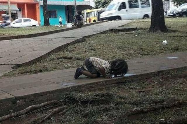Bức ảnh bé gái quỳ gối, uống vũng nước trên đường vì đói khát khiến cả thế giới rúng động-1