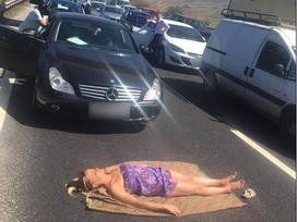 Bị kẹt xe 3 tiếng, cô gái tranh thủ nằm phơi nắng giữa đường