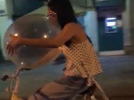 Cô gái vừa đi xe đạp, vừa thản nhiên hít bóng cười trên phố Hà Nội
