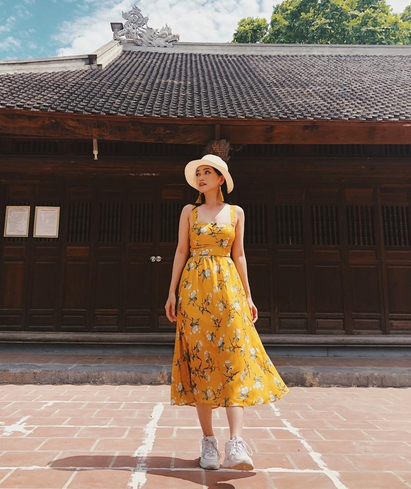Sĩ Thanh mang âm hưởng mùa hè vào trong set đồ nữ tính cùng váy vàng họa tiết hoa nhí, khuyên tai ton-sur-ton.