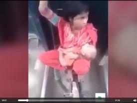 Xem mẹ trẻ bế con ngồi 'vắt vẻo' giữa hai toa tàu