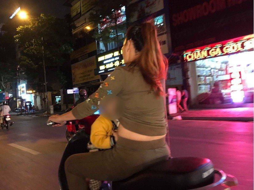 Bà mẹ 1 tay lái xe máy, 1 tay ôm con bú trên đường-1
