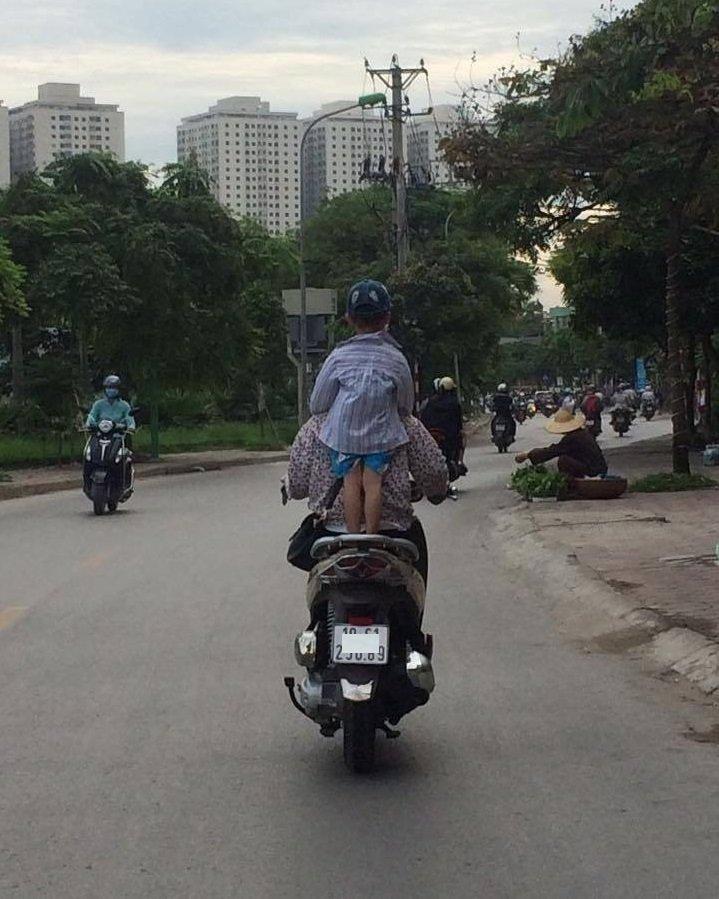 Bà mẹ 1 tay lái xe máy, 1 tay ôm con bú trên đường-3