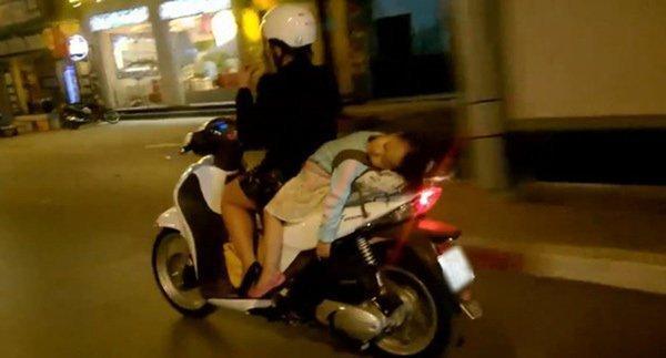 Bà mẹ 1 tay lái xe máy, 1 tay ôm con bú trên đường-4
