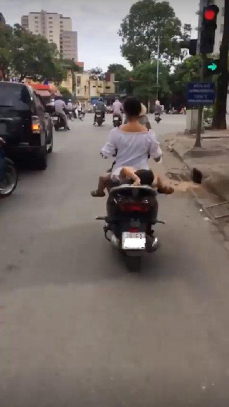 Bà mẹ 1 tay lái xe máy, 1 tay ôm con bú trên đường-5