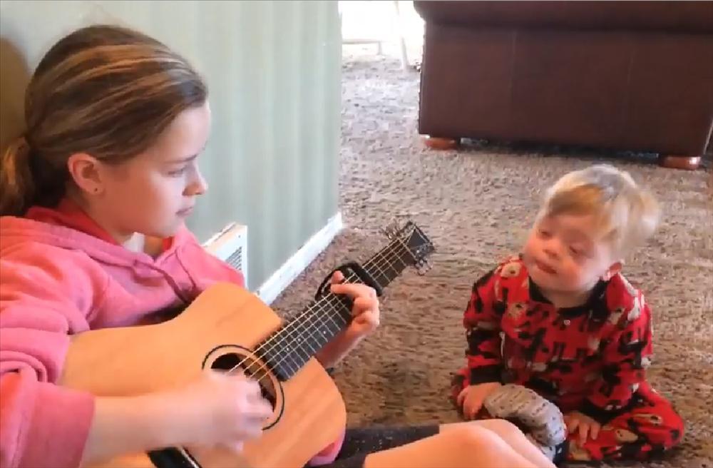Cô bé đàn hát cho cậu em trai bị Down, khoảnh khắc gây xúc động khiến ai cũng phải bật khóc-1