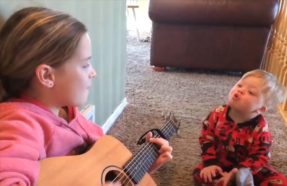 Cô bé đàn hát cho cậu em trai bị Down, khoảnh khắc gây xúc động khiến ai cũng phải bật khóc-2