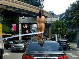 Không mảnh vải che thân, cô gái trẻ nhảy múa trên nóc ô tô khiến người xung quanh sốc nặng