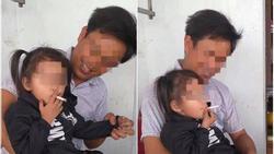 Bé gái tay cầm thuốc đưa lên miệng hút trong sự cười đùa của người đàn ông ngồi cạnh khiến nhiều người bức xúc