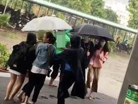 Ấm lòng hình ảnh bác bảo vệ mặc áo mưa, che ô cho sinh viên