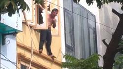 Clip: Thanh niên Thủ đô trèo ra ngoài cửa sổ tầng 3 đứng vắt vẻo, lúc thì đu dây như khỉ, khi thì cầm dao tự dí vào cổ rồi chửi bới inh ỏi