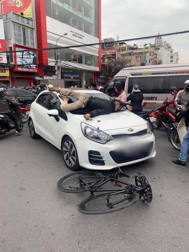 Va chạm giao thông nhưng không hòa giải được, chủ xe đạp leo lên nắp capo ô tô nằm... ăn vạ-1