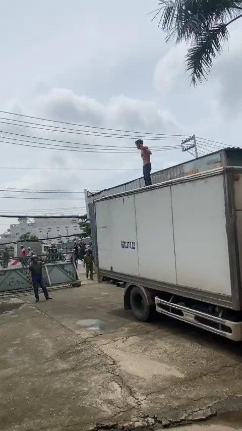 Người đàn ông ngáo ngơ, cầm hung khí leo lên nóc xe tải la hét, nhún nhảy-1
