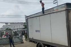 Người đàn ông ngáo ngơ, cầm hung khí leo lên nóc xe tải la hét, nhún nhảy