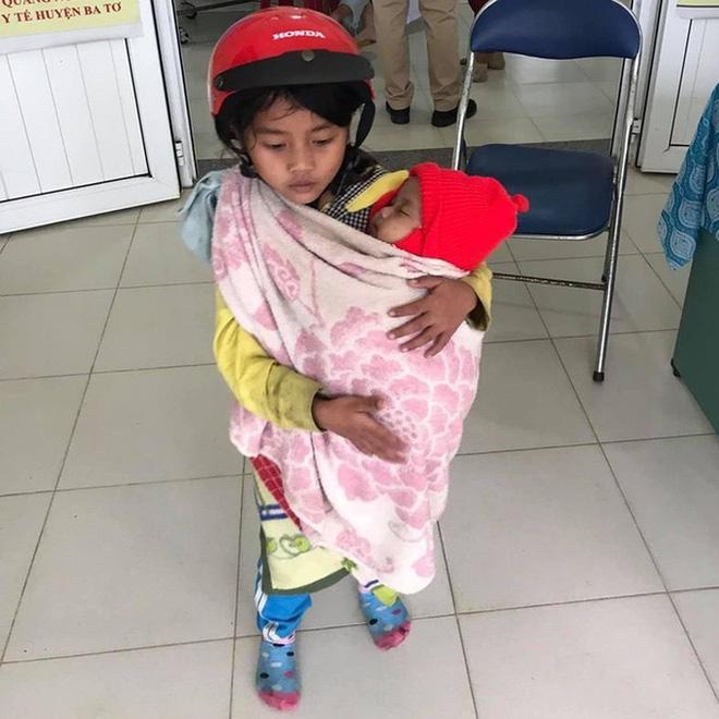 Cảm động chị gái 7 tuổi địu em 5 tháng tuổi đi tiêm phòng: Bất ngờ về mẹ bé-1