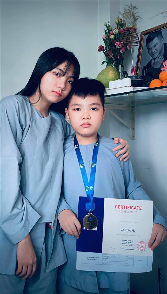 2 con Vân Quang Long cầm giấy khen đứng trước bàn thờ bố-1