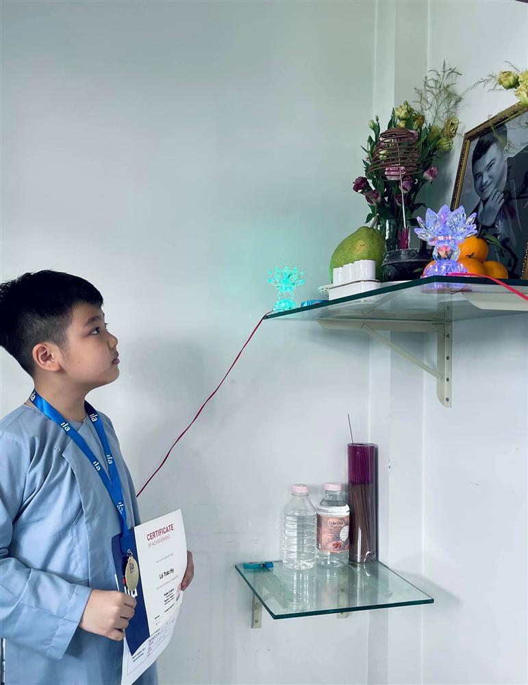 2 con Vân Quang Long cầm giấy khen đứng trước bàn thờ bố-2