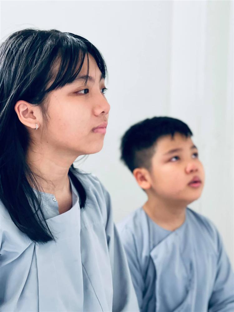 2 con Vân Quang Long cầm giấy khen đứng trước bàn thờ bố-3