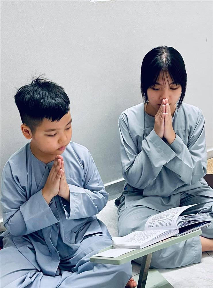 2 con Vân Quang Long cầm giấy khen đứng trước bàn thờ bố-4