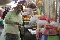 Người dân mặc áo mưa, trùm kín khi đi chợ giữa nắng 37 độ C