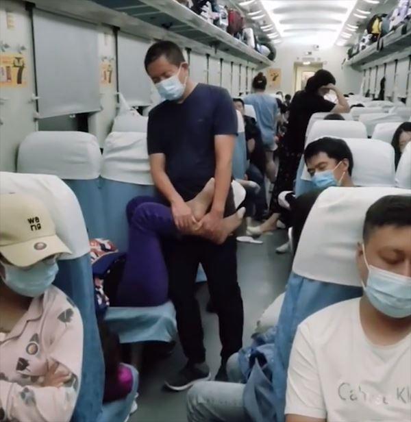 Chồng đứng ôm chân giúp cho vợ ngủ cả đêm trên tàu lửa-1