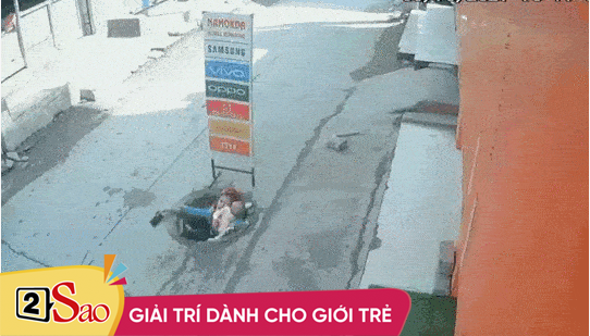 Clip: Vừa đi vừa nghe điện thoại, mẹ bế con rơi xuống cống thoát nước